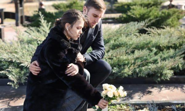Dwoje młodych ludzi na cmentarzu podczas składania kwiatów na grób bliskiej osoby