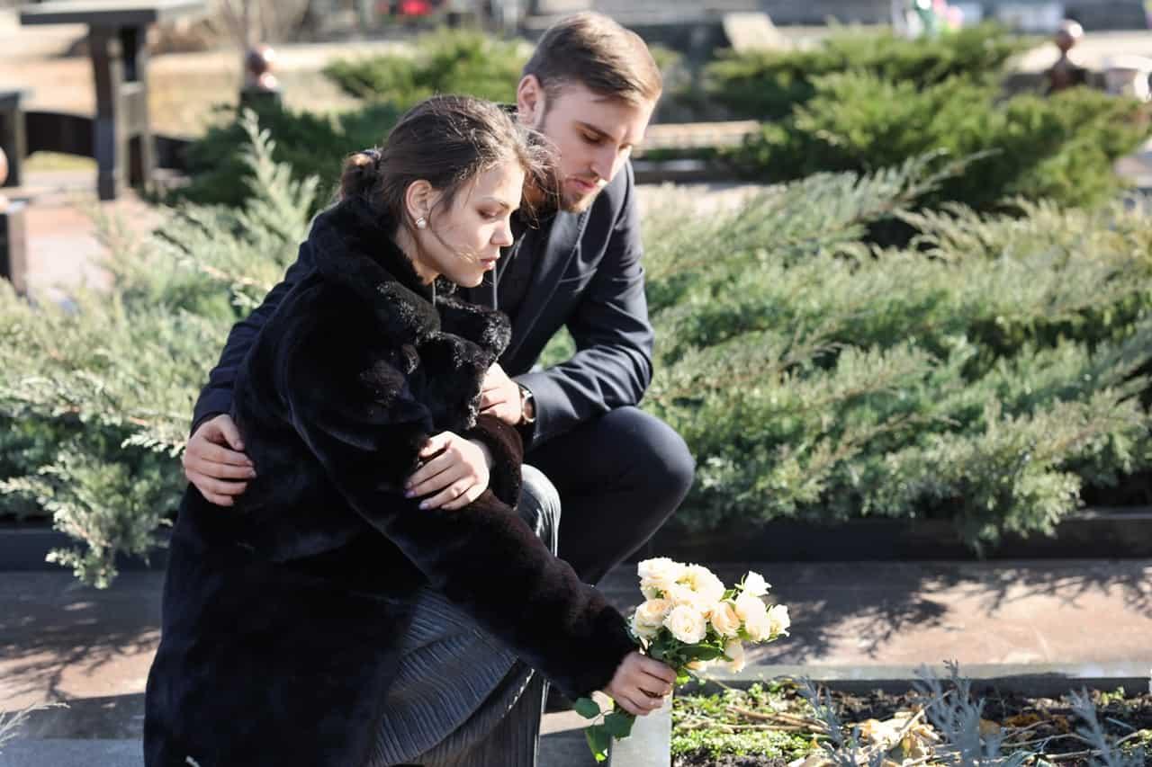 Dwoje młodych ludzi nacmentarzu podczas składania kwiatów nagrób bliskiej osoby