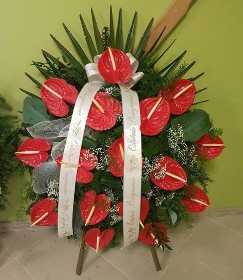 duży wieniec pogrzebowy z czerownych kwiatów z napisem na szarfie