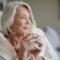 starsza uśmiechnięta kobieta z kubkiem herbaty w dłoniach