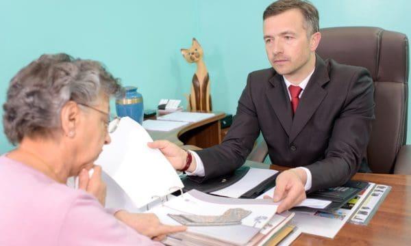 pracownik zakładu pogrzebowego pomaga wybrać starszej kobiecie nagrobek z firmowego katalogu