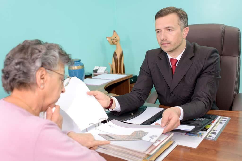 pracownik zakładu pogrzebowego pomaga wybrać starszej kobiecie nagrobek zfirmowego katalogu