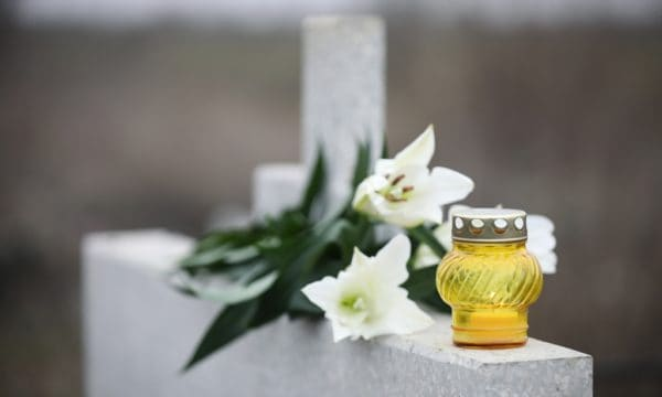 znicz i kwiaty na nagrobku